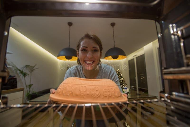 Schöne junge Frau, die etwas in den Ofen einsetzt zu kochen stockfotos