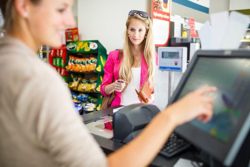 Schöne junge Frau, die für ihre Lebensmittelgeschäfte am Zähler zahlt stockfoto