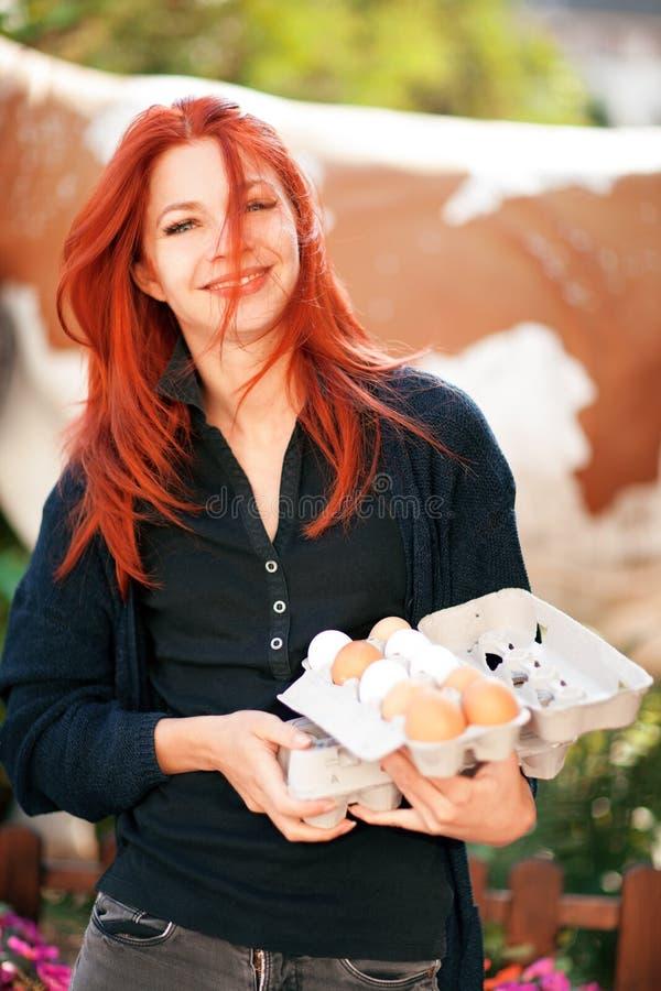 Schöne junge Frau, die frische Eier an einem Bauernhof kauft stockbilder