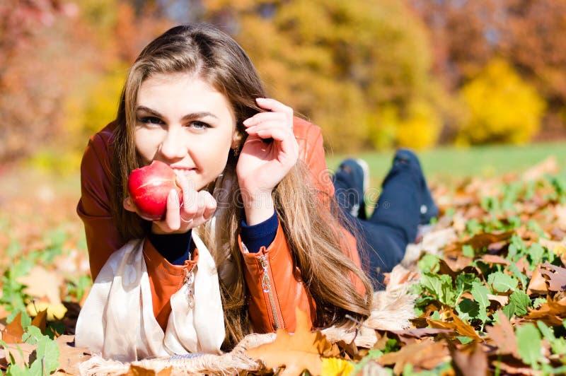 Schöne junge Frau, die frischen roten Apfel isst stockfotografie