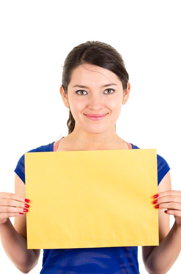 Schöne junge Frau, die gelbes leeres Zeichen hält lizenzfreie stockfotografie