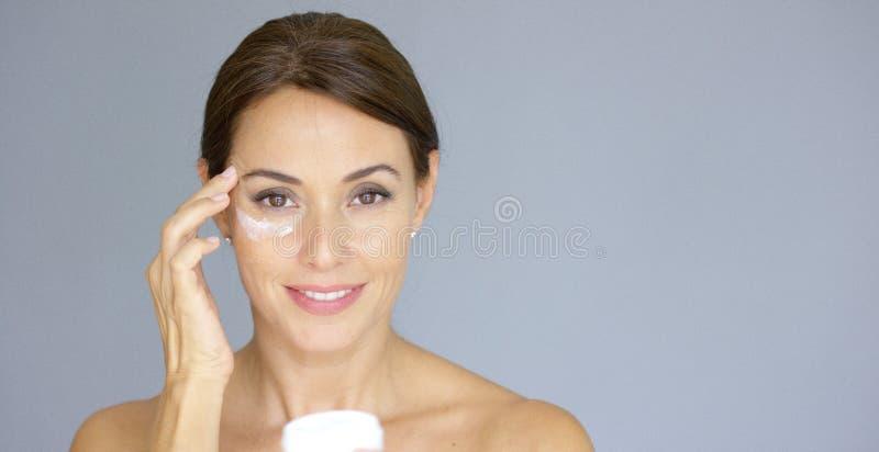 Schöne junge Frau, die Gesichtscreme aufträgt stockfoto