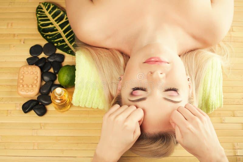 Schöne junge Frau, die Gesichtsmassage an einem Badekurortsalon empfängt stockbild