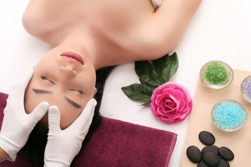 Schöne junge Frau, die Gesichtsmassage im Badekurortsalon empfängt lizenzfreies stockbild