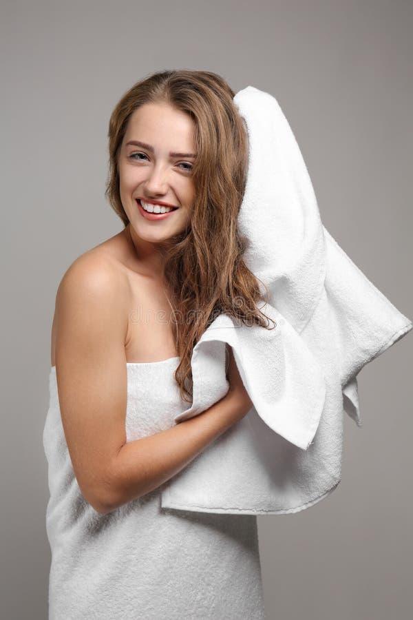 Schöne junge Frau, die Haar mit Tuch nach Dusche auf grauem Hintergrund abwischt stockbilder