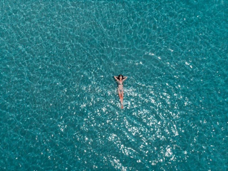 Schöne junge Frau, die in haarscharfes Wasser, Luftschuß schwimmt lizenzfreie stockbilder
