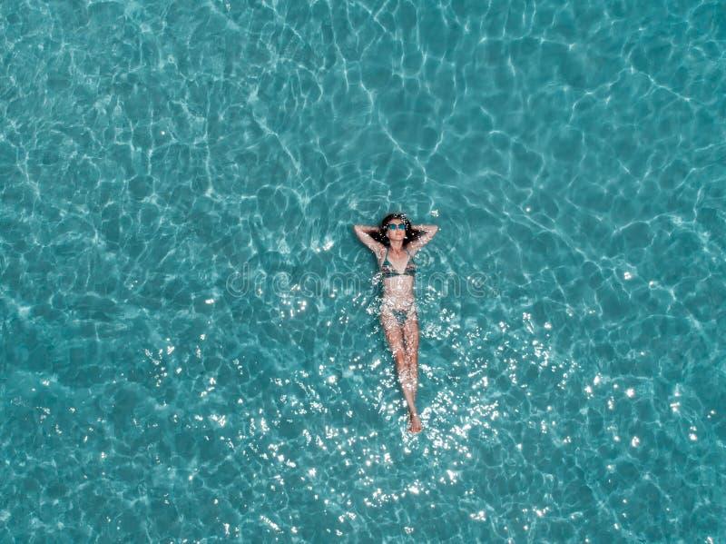 Schöne junge Frau, die in haarscharfes Wasser, Luftschuß schwimmt lizenzfreie stockfotos