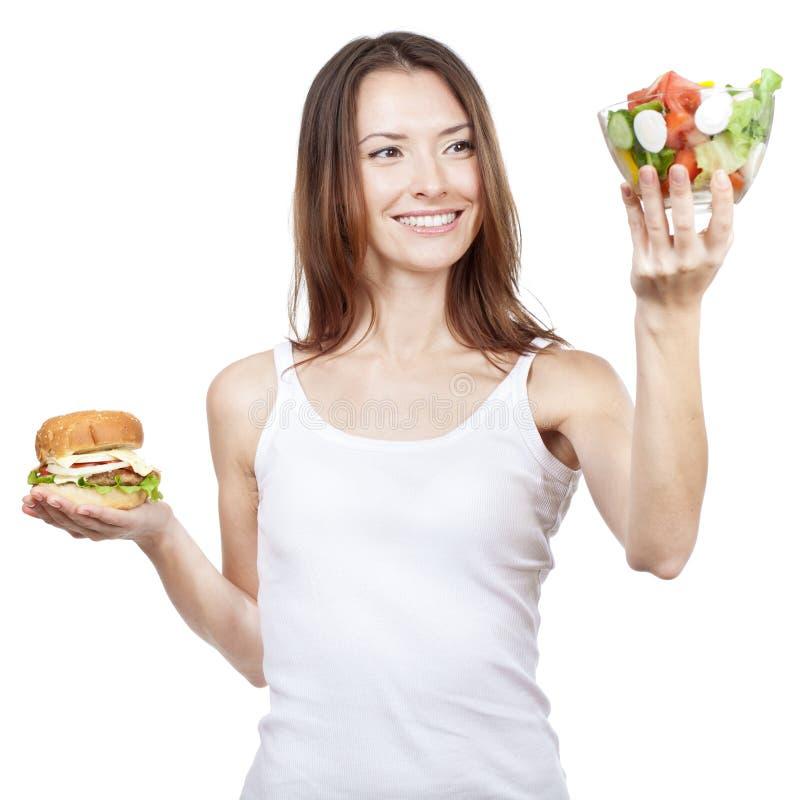 Schöne junge Frau, die Hamburger und Salat hält lizenzfreie stockfotografie
