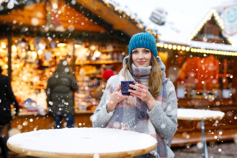 Schöne junge Frau, die heißen Durchschlag, Glühwein auf deutschem Weihnachtsmarkt trinkt Glückliches Mädchen in der Winterkleidun stockfotografie