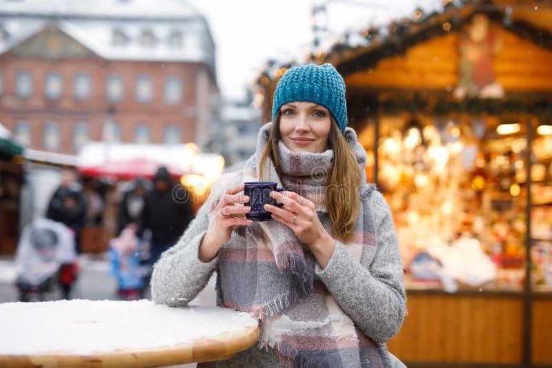 Schöne junge Frau, die heißen Durchschlag, Glühwein auf deutschem Weihnachtsmarkt trinkt Glückliches Mädchen in der Winterkleidun lizenzfreies stockbild