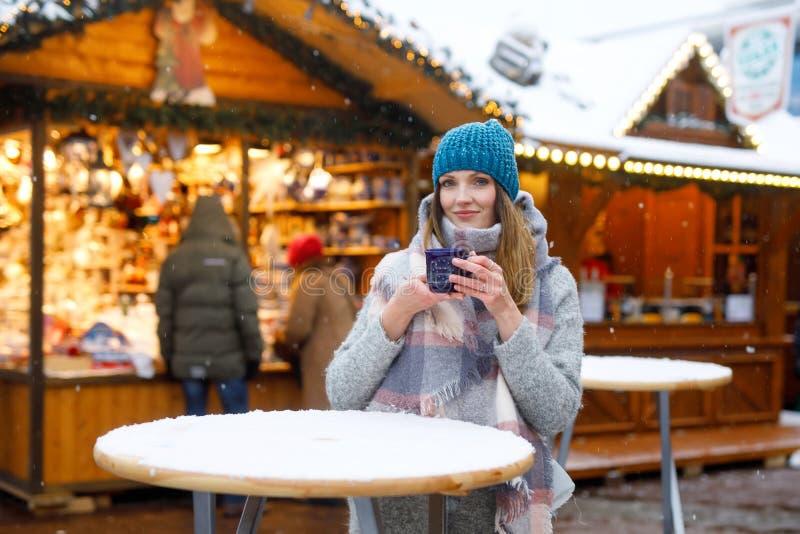 Schöne junge Frau, die heißen Durchschlag, Glühwein auf deutschem Weihnachtsmarkt trinkt Glückliches Mädchen in der Winterkleidun stockbilder