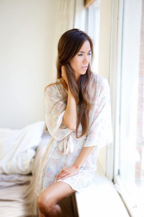 Schöne junge Frau, die heraus Fenster schaut stockfoto