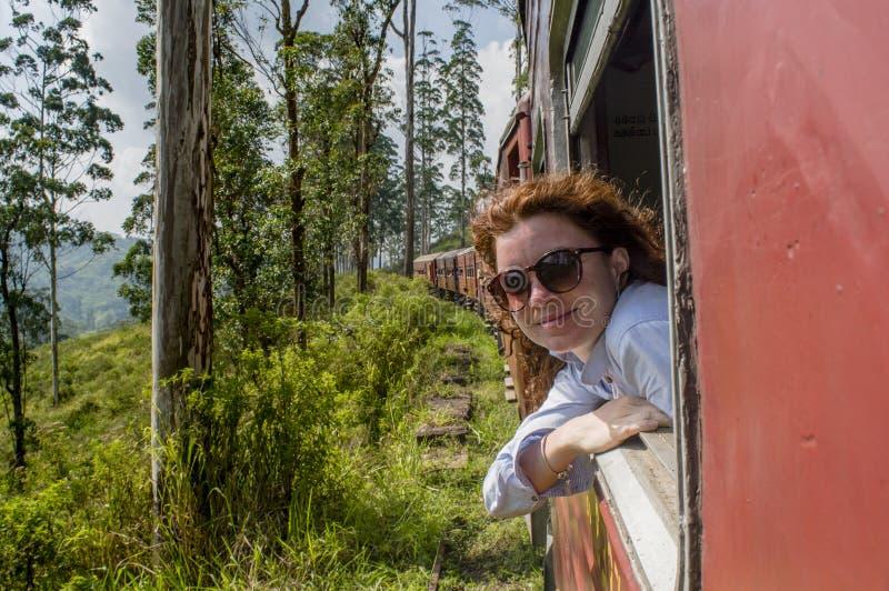 Schöne junge Frau, die heraus vom Fenster im Zug schaut stockfotografie
