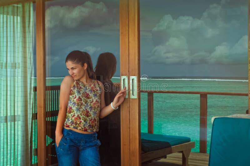 Schöne junge Frau, die heraus zum Meer schaut stockbilder