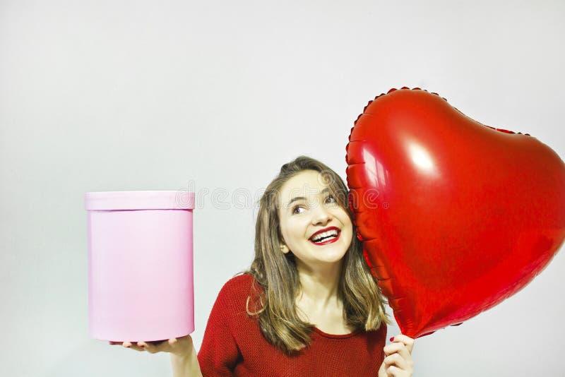 Schöne junge Frau, die Herzformluftballon und -Geschenkbox auf einem grauen Hintergrund hält stockfotos