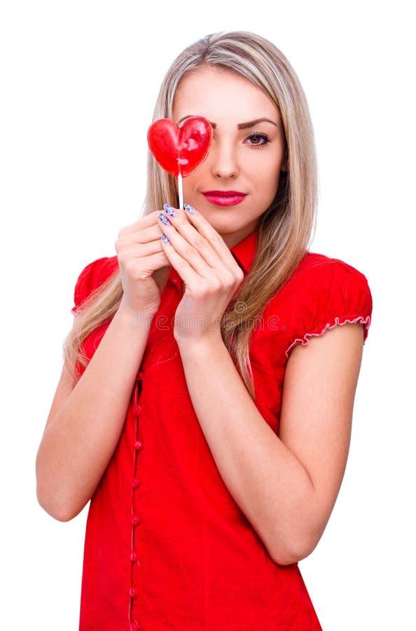 Schöne junge Frau, die Herzformlutscher auf Weiß hält stockbilder