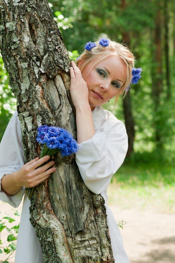 Schöne junge Frau, die hinter dem Baum sich versteckt lizenzfreie stockfotografie