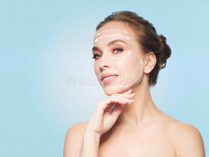 Schöne junge Frau, die ihr Gesicht berührt lizenzfreie stockfotografie