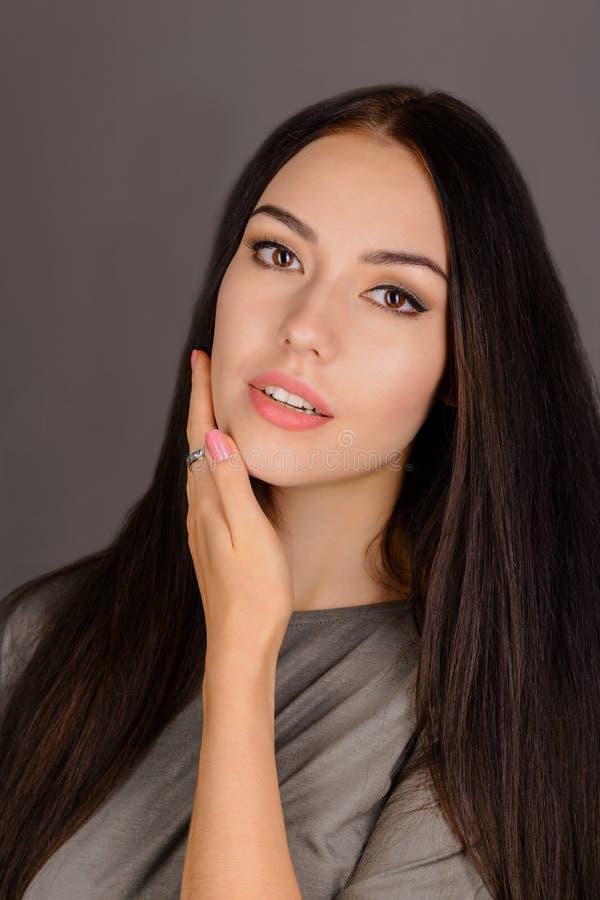 Schöne junge Frau, die ihr Gesicht berührt Frische gesunde Haut lizenzfreie stockbilder