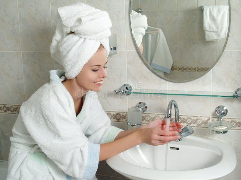 Schöne junge Frau, die ihr Gesicht mit Wasser wäscht stockfoto