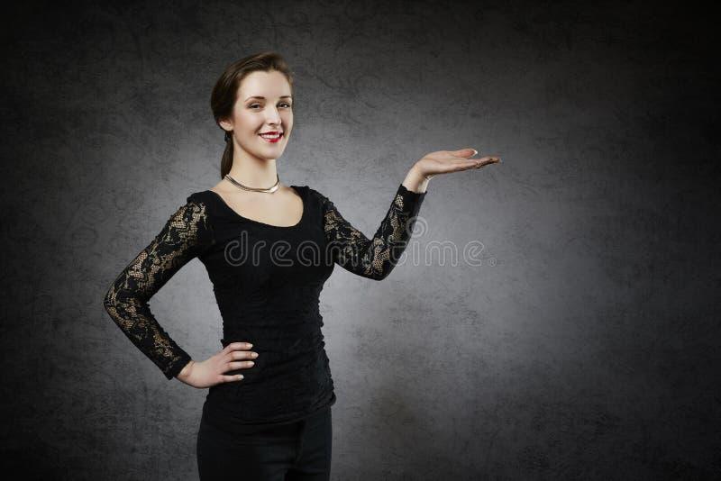 Schöne junge Frau, die Ihr Produkt zeigt lizenzfreies stockfoto