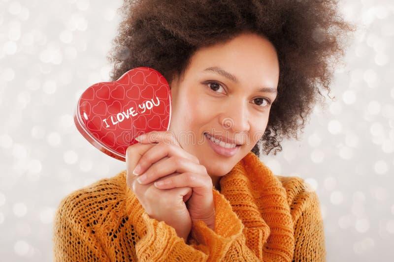 Schöne junge Frau, die ihre Geschenkbox hält lizenzfreie stockbilder
