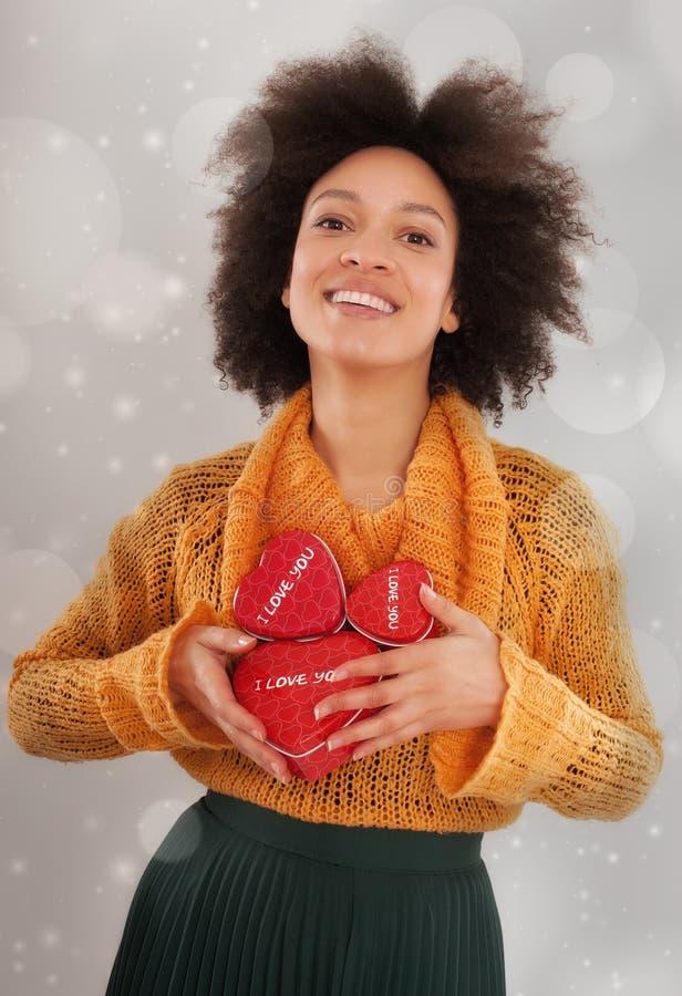 Schöne junge Frau, die ihre Geschenkbox hält stockbild