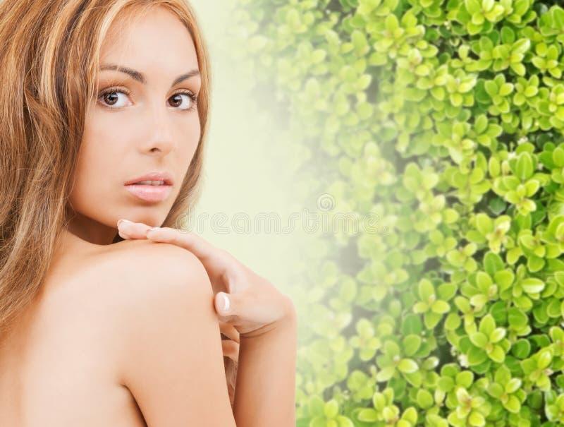 Schöne junge Frau, die ihre Gesichtshaut berührt stockfotografie