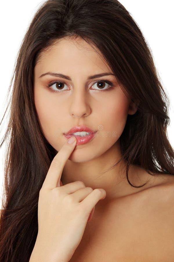 Schöne junge Frau, die ihre Lippen berührt stockfoto