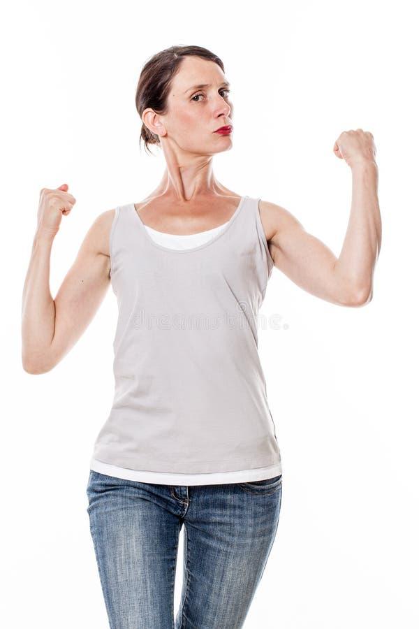 Schöne junge Frau, die ihre Muskeln und Stärke mit Stolz zeigt stockfotos
