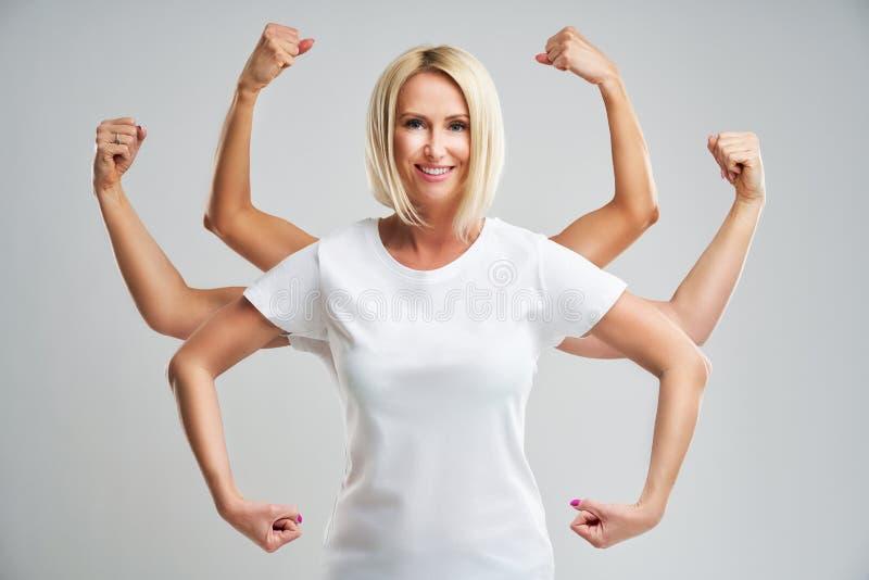 Schöne junge Frau, die ihre Muskulosität zeigt und Kamera betrachtet lizenzfreies stockbild