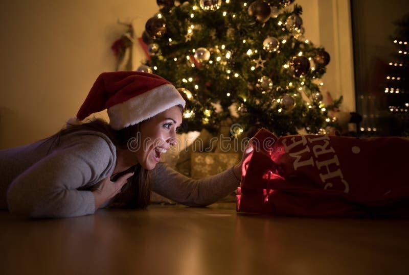 Schöne junge Frau, die ihrem Weihnachtsgeschenk überrascht betrachtet stockfotos