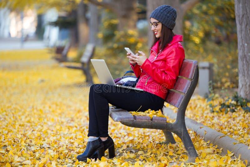 Schöne junge Frau, die ihren Handy beim Arbeiten mit Laptop im Herbst verwendet lizenzfreies stockfoto