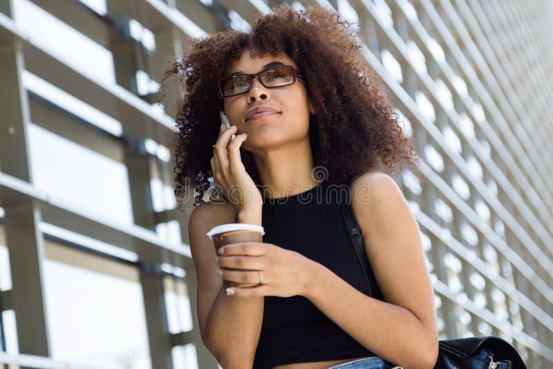 Schöne junge Frau, die ihren Handy in der Straße verwendet lizenzfreie stockfotos