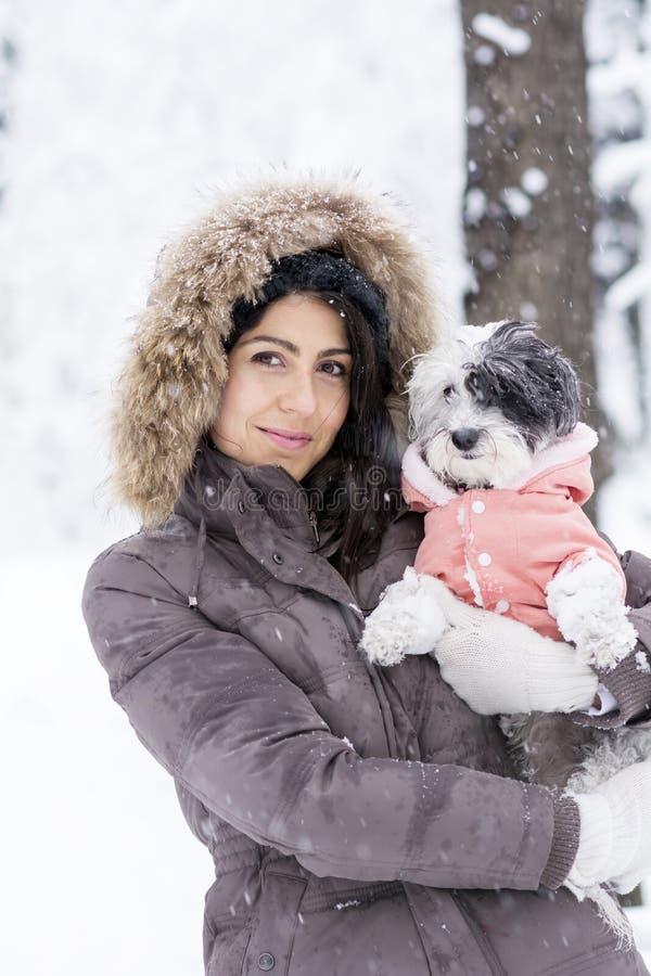 Schöne junge Frau, die ihren kleinen weißen Hund im Winterwald umarmt snowing lizenzfreie stockfotografie