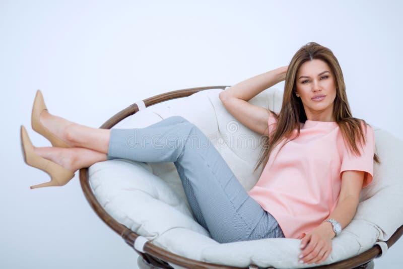 Schöne junge Frau, die im bequemen Stuhl sitzt lizenzfreie stockbilder