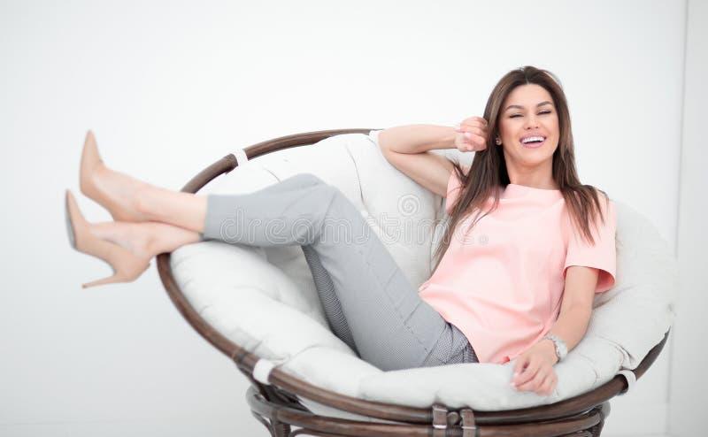 Schöne junge Frau, die im bequemen Stuhl sitzt stockfotografie