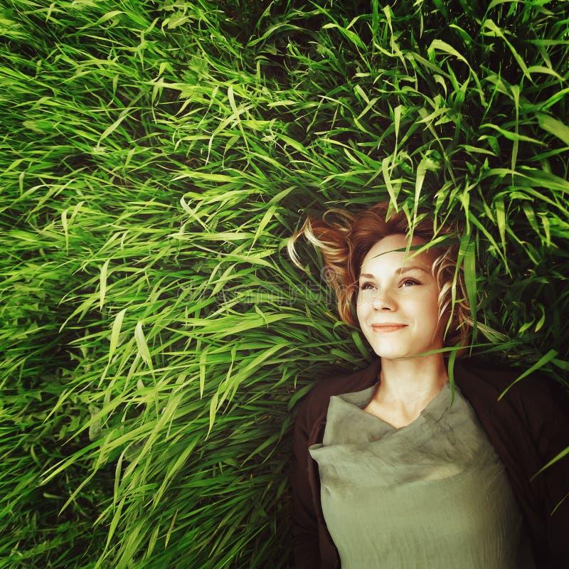 Schöne junge Frau, die im Gras liegt. Retro- Effekt Instagram stockbilder