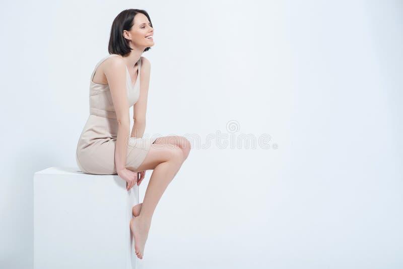 Schöne junge Frau, die im Kleid aufwirft stockfotografie