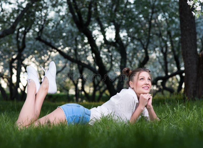 Schöne junge Frau, die im Park auf dem Gras, denkend an etwas oder das Träumen liegt lizenzfreies stockbild