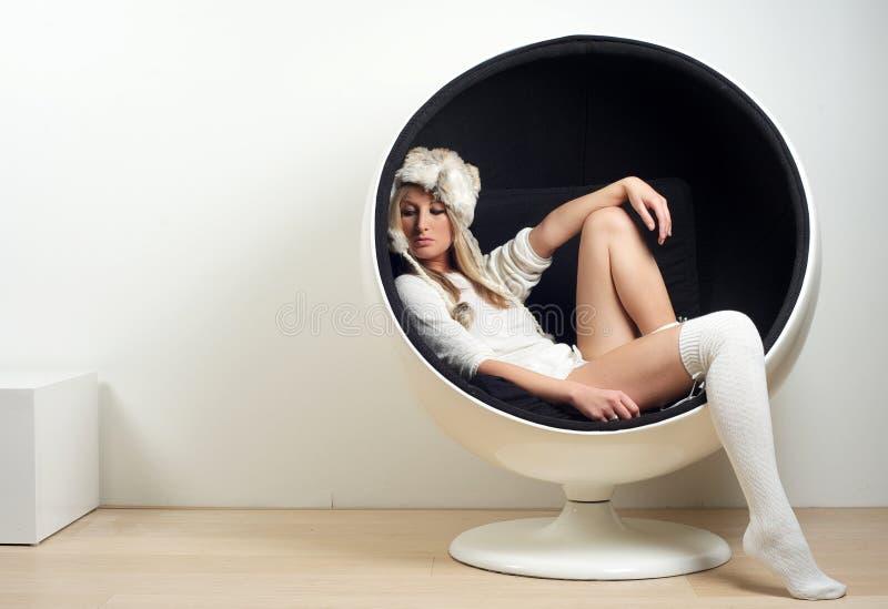 Schöne junge Frau, die im Retro- modischen Stuhl sitzt stockbilder