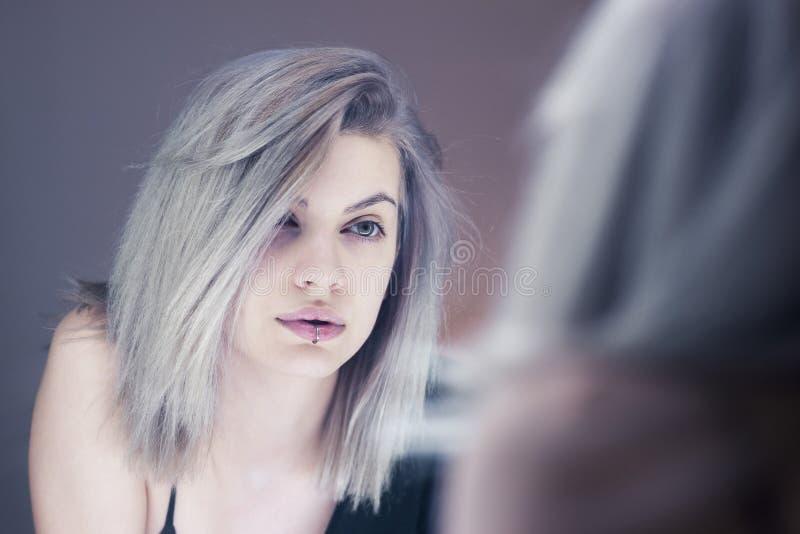Schöne junge Frau, die im Spiegel schaut lizenzfreie stockbilder