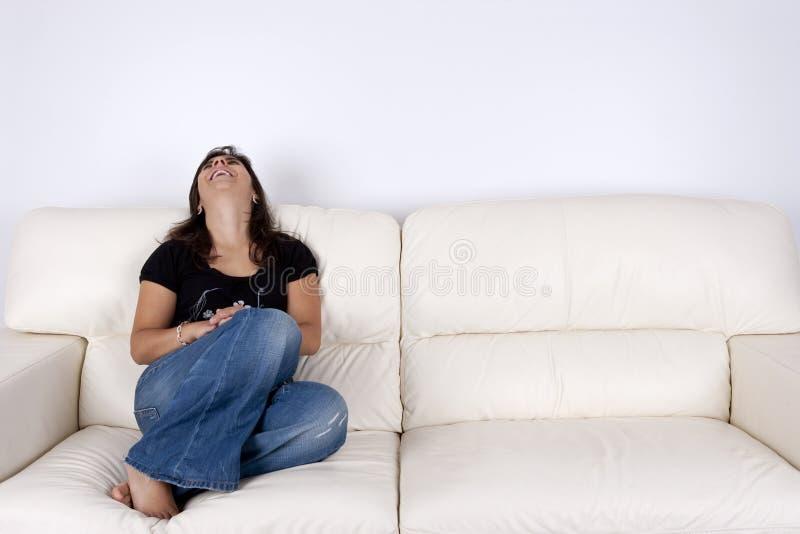 Schöne junge Frau, die im weißen Sofa sitzt stockbild