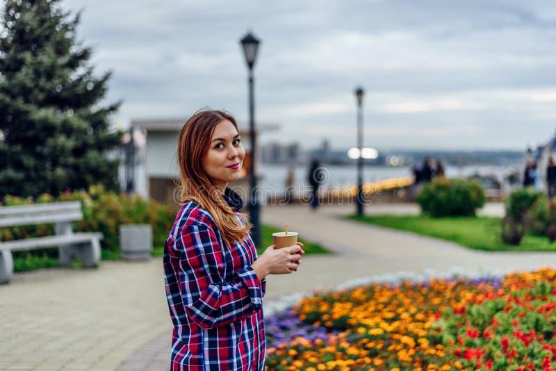Schöne junge Frau, die Kaffeetasse hält und im Park lächelt stockfoto