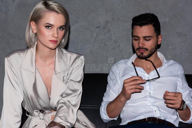 schöne junge Frau, die Kamera beim Sitzen auf Couch mit Geschäftsmann betrachtet stockbild