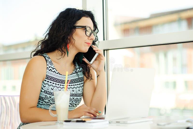 Schöne junge Frau, die Laptop verwendet und am Handy spricht stockfoto