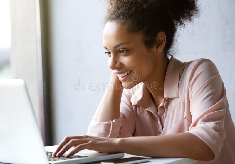 Schöne junge Frau, die Laptopschirm lächelt und betrachtet stockbild