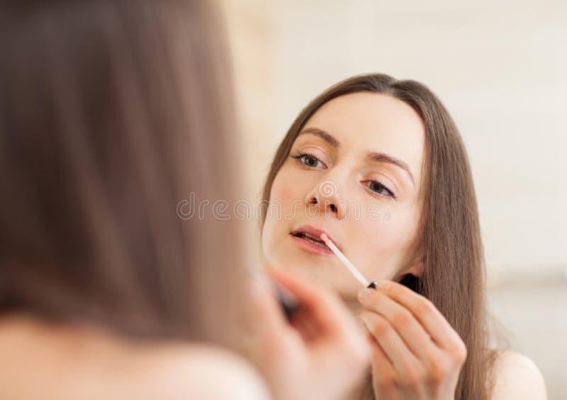 Schöne junge Frau, die lipgloss anwendet lizenzfreie stockfotografie