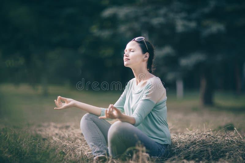 Sch?ne junge Frau, die in Lotussitz in Sommer Park meditiert lizenzfreie stockbilder
