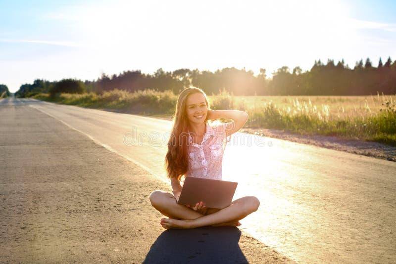 Schöne junge Frau, die mit Laptop sitzt und auf der Straße hinausgeht über den Horizont bei Sonnenuntergang lächelt lizenzfreies stockbild